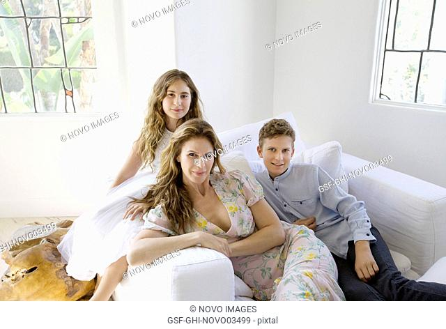 Portrait of Mother and her Two Children Sitting on Upholstered Chair