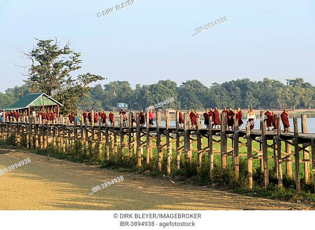 Locals and monks on a teak bridge, U Bein Bridge, over Thaungthaman Lake, Amarapura, Mandalay Division, Myanmar