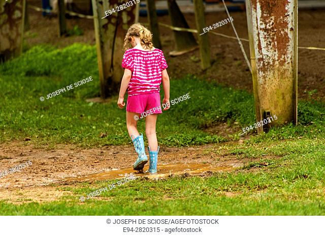 A partial view of a 6 year old girl wearing rubber boots, splashing and playing in a mud puddle