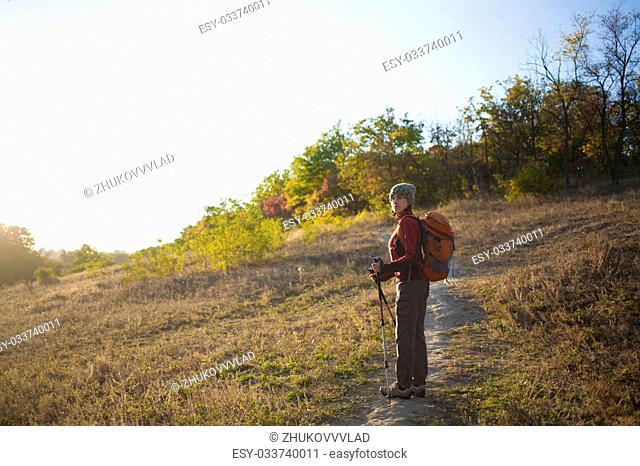 Woman with a backpack walking along the road in the woods