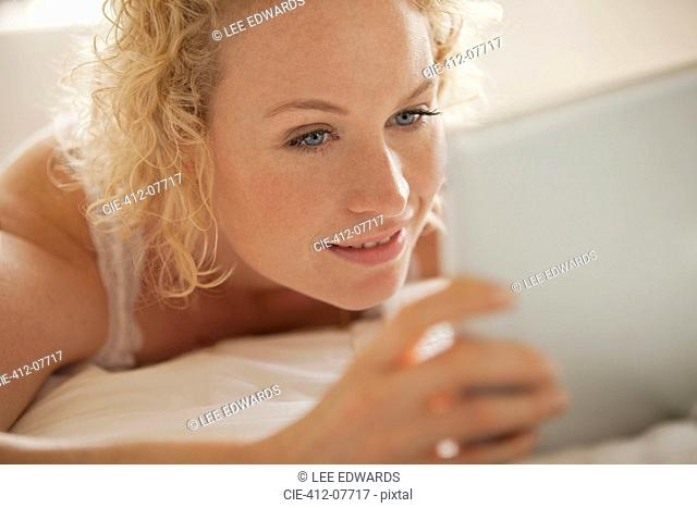 Close up of woman using digital tablet in bed
