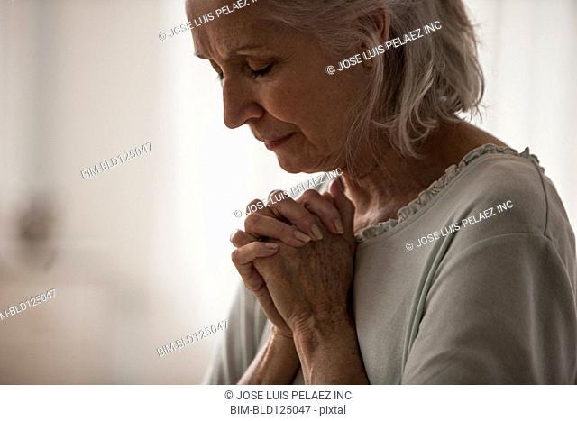 Senior Caucasian woman praying