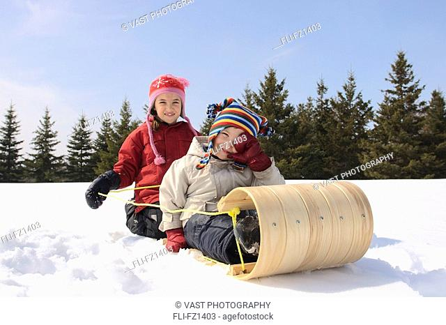 Brother and sister riding on sled, King City, Ontario