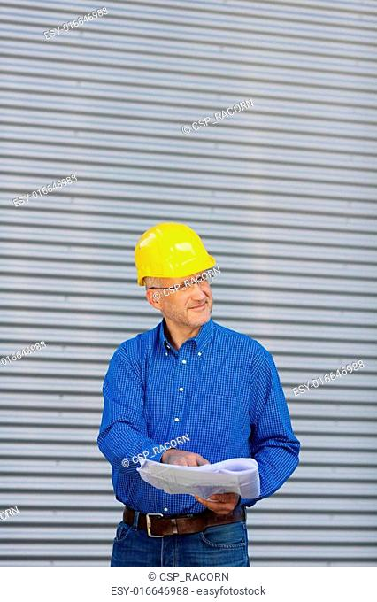 Architect Holding Blueprint While Looking Away