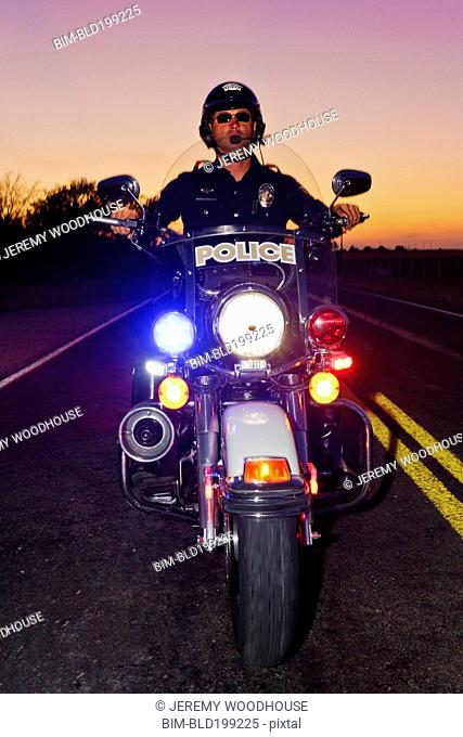 Caucasian policeman riding on motorcycle