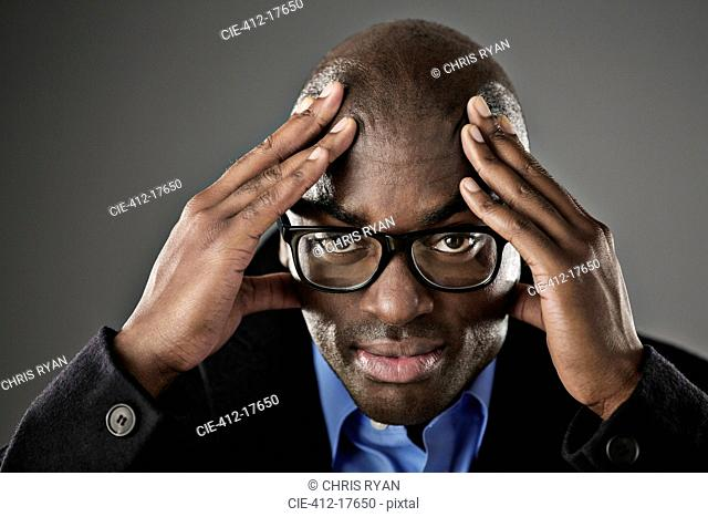Portrait of stressed businessman with head in hands
