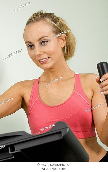 Caucasian woman in early 20s exercising on a cardiovascular machine