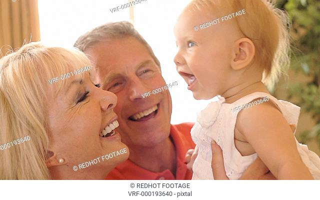 Grandparents and baby granddaughter playing on sofa indoors
