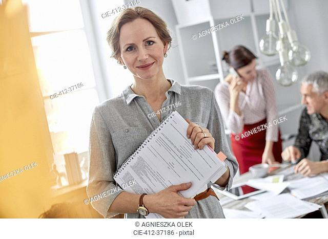 Portrait smiling businesswoman with paperwork in office meeting