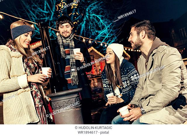 Four friends drinking punch at Christmas Market