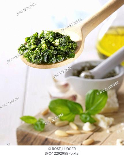 Pesto on a wooden spoon above a wooden board with basil, pine nuts and olive oil