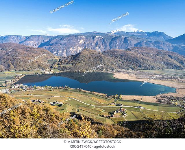 Lake Kalterer See (Lago di Caldaro) during autumn. The Dolomites and the Bletterbach canyon, both usesco world heritage sites in the background Europe