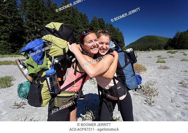 Two sisters hug and enjoy the end of the day's hike arriving at San Josef Bay along the Cape Scott Trail