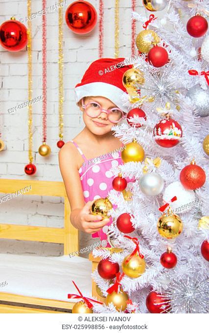 Six year old girl hangs balls on the Christmas tree Christmas snow
