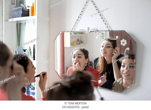 Young women friends getting ready, applying makeup in bathroom mirror