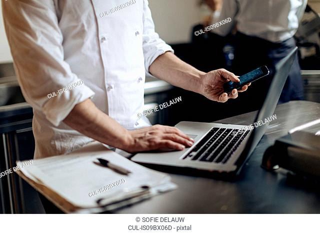 Chef using laptop and cellphone in kitchen