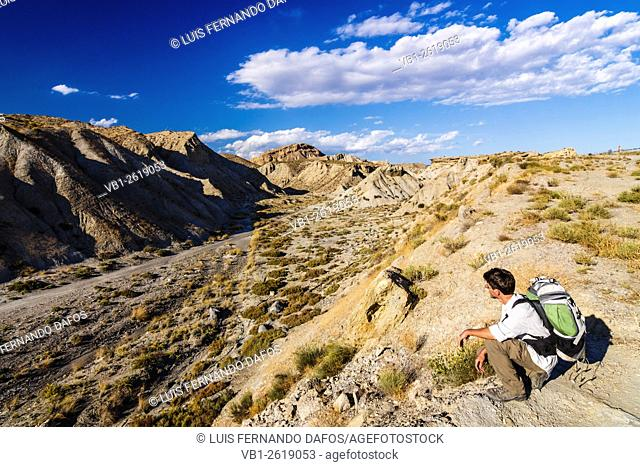Hiker looking at a dry creek in Tabernas desert, one of the dryest areas in Europe. Tabernas, Almeria, Andalusia, Spain