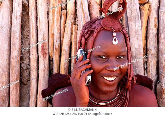 Namibia Africa remote nomadic Himba tribe young women with braids on modern cell phone and traditional dress in desert of Hartmann Berge in Namib Desert