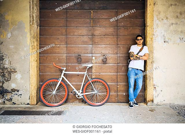 Young man with a bicycle in the city