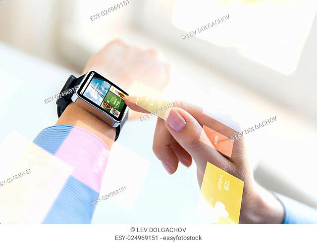 business, modern technology, media, internet and people concept - close up of female hands setting smart watch with news web page on screen at office