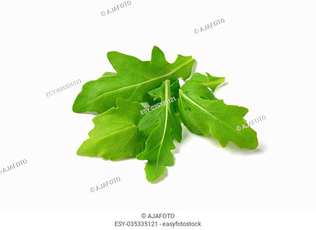 handful of fresh arugula leaves on white background