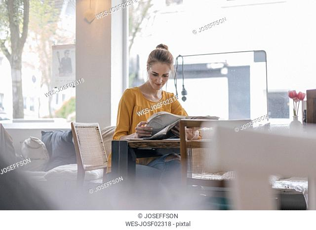 Young woman sitting in coworking space, reading newspaper