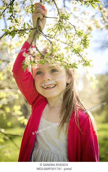 Portrait of smiling girl holding blossoming twig