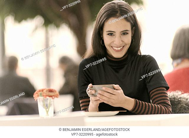 portrait of happy laughing woman holding coffee cup while sitting at table in café, in Munich, Germany