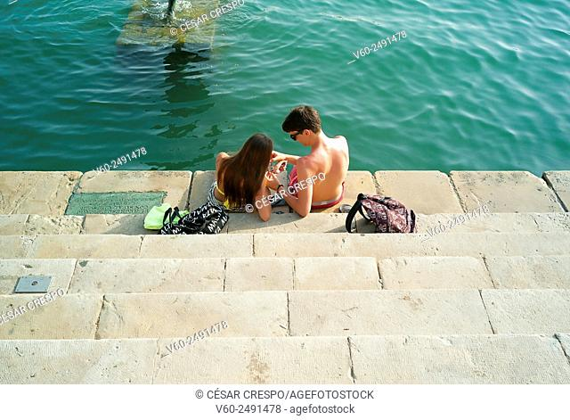 -Couple sitting on the stairs- Alicante's Port (Spain)
