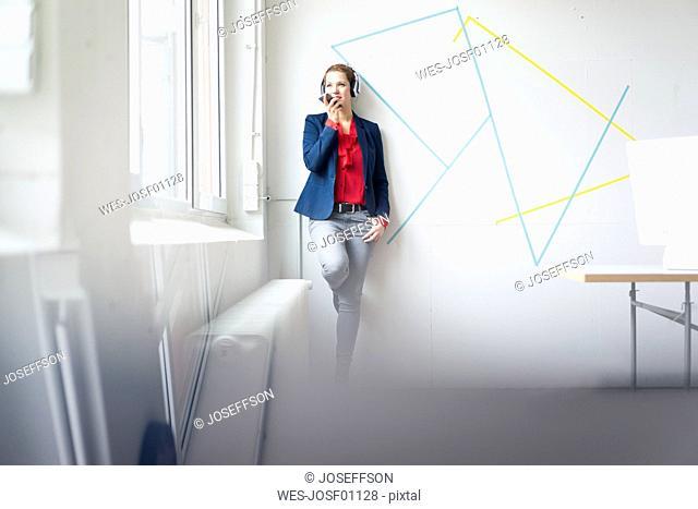 Businesswoman making a call, wearing headphones