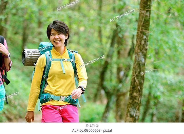 Young Japanese woman trekking in the woods