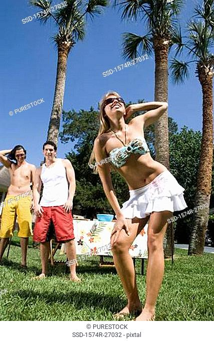 Young men watching a cheerful young woman dancing on lawn
