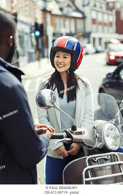 Smiling young woman in helmet on motor scooter, talking to friend on urban street