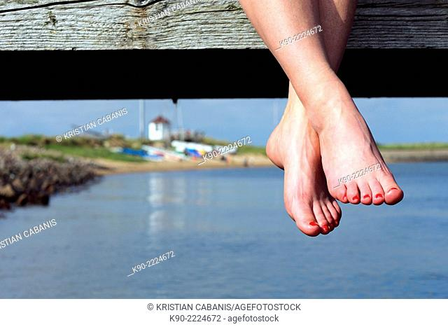 Feet and legs hanging from a jetty at Stenodde harbor, North Frisian, Schleswig-Holstein, Germany, Europe