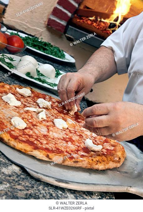 Chef garnishing pizza with cheese