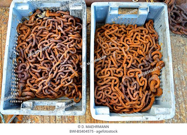 rusty chains in plastic boxes, France, Brittany