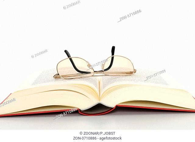 Aufgeblättertes Buch mit Brille / Open book with glasses