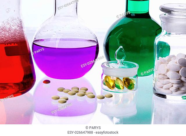 Laboratory glassware with liquids of different colors and tablets on white background