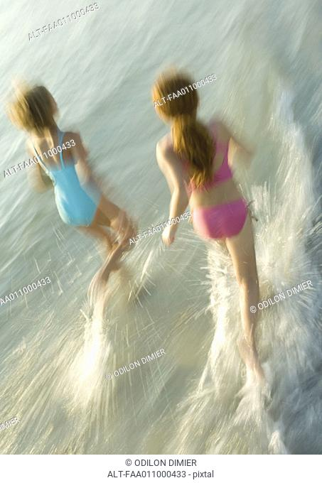 Two girls running in surf
