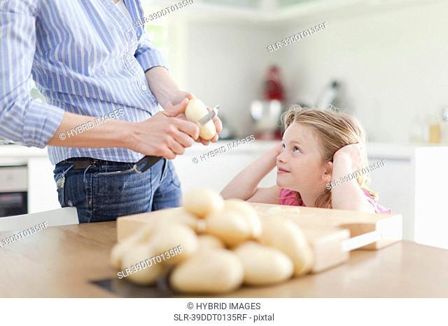 Mother helping daughter peel potatoes