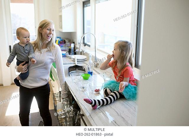 Smiling mother watching daughter eating on kitchen counter