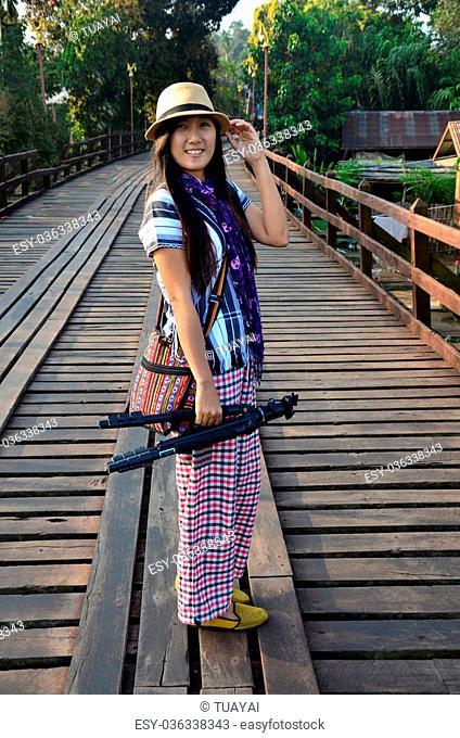 Thai Women with tripod portrait at Saphan Mon Wooden Bridge at Sangkhlaburi in Kanchanaburi, Thailand