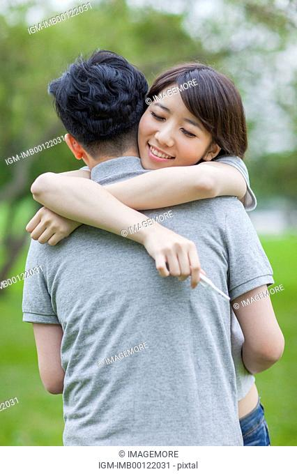 Young couple embracing with smile