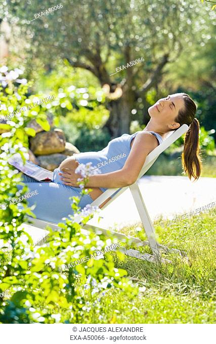 Woman relaxing in the garden on her louge chair in the sun while caressing her belly