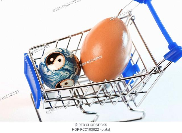 Close-up of a brown egg and a yin yang ball in a shopping cart