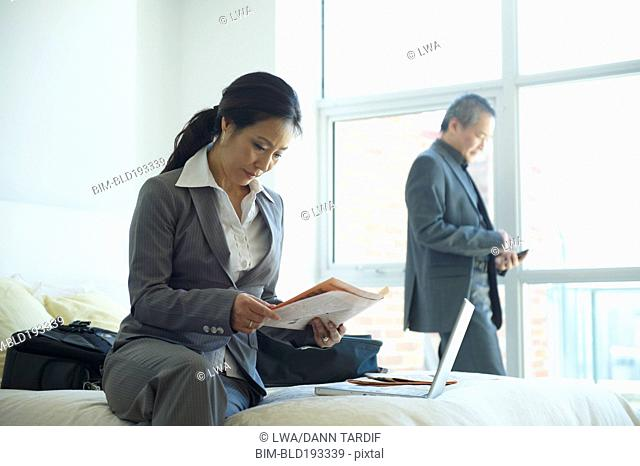 Asian businessman and businesswoman working in hotel room