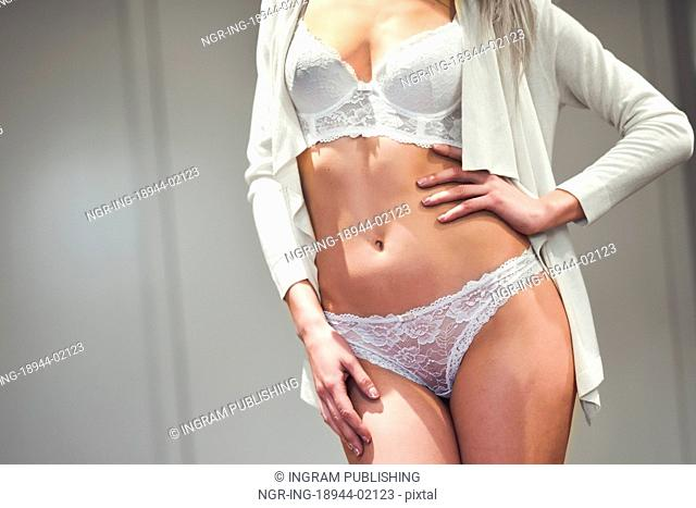 Unrecognizable young woman with beautiful body in white lingerie