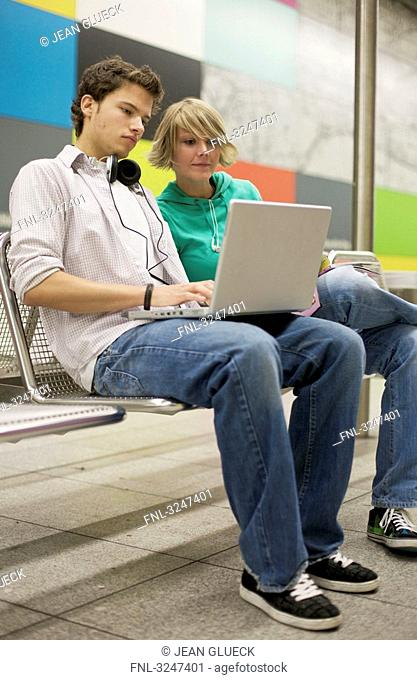 Teenager couple using laptop at underground station, low-angle view