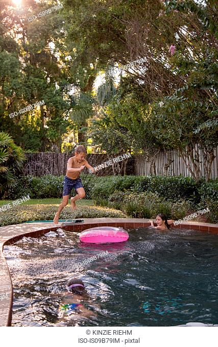 Children swimming in garden pool, young boy jumping in, mid-air