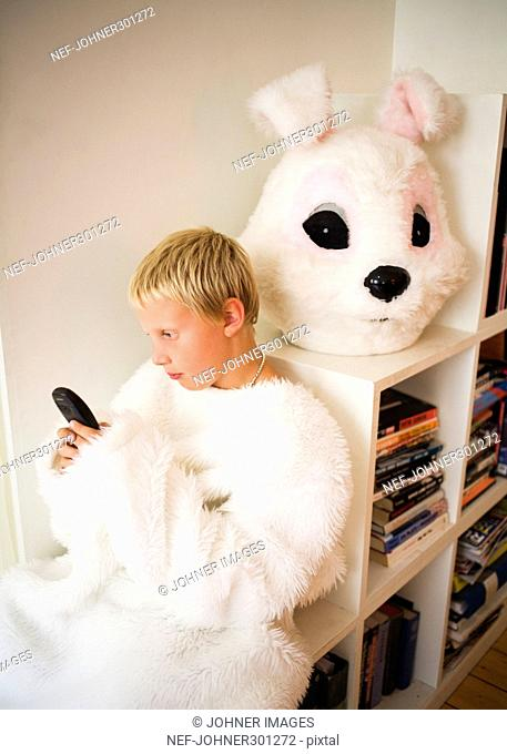 A boy in a bunny costume sending a text message